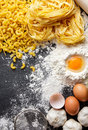 Raw homemade macaroni pasta and fettucine with ingredients Royalty Free Stock Photo