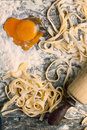 Raw homemade pasta with with egg yolk as heart top view on flour and over old wooden table see series Royalty Free Stock Photos