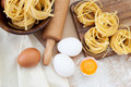 Raw homemade pasta fresh tagliatelle eggs and rolling pin on a table Royalty Free Stock Image