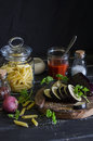 Raw ingredients for cooking Italian pasta with eggplant - penne pasta, eggplant, onion, tomato sauce, spices and herbs. On a dark Royalty Free Stock Photo
