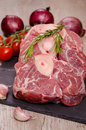 Raw italian ossobuco with red onions and garlic cloves Royalty Free Stock Images