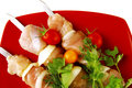 Raw kebabs on red plate chicken served with cherry and greenery Royalty Free Stock Photography