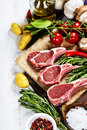 Raw lamb cutlets with vegetables herbs and spices Royalty Free Stock Image