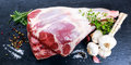 Raw lamb leg on blue stone background Royalty Free Stock Photo