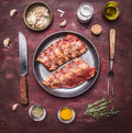 Raw lamb ribs on a frying pan, with a knife and fork for the meat, spices and herbs wooden rustic background top view Royalty Free Stock Photo