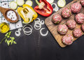 Raw meat balls with herbs and onions on a cutting board with bell peppers, butter,  on wooden rustic background top view Royalty Free Stock Photo