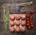 Raw meat balls with vegetables, butter and herbs on wooden rustic background top view close up Royalty Free Stock Photo