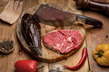 Raw meat next to the axe and vegetables Royalty Free Stock Photo