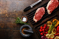 Raw meat Steak on iron grill and Grilled vegetables Royalty Free Stock Photo
