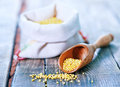 Raw millet in wooden spoon and on a table Royalty Free Stock Photos