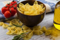 Raw pasta farfalle in bowl on white table selective focus Stock Photography