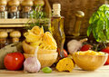 Raw pasta with vegetables on wooden table Royalty Free Stock Photos