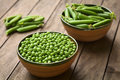 Raw peas lat pisum sativum and closed peapods in bowls selective focus focus into the middle of the Stock Images