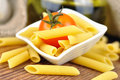Raw penne pasta in a small bowl, selective focus Stock Photos