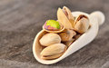 Raw pistachio nuts a wooden spoon of on a old wooden background Royalty Free Stock Image