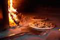 Raw pizza lay down stove with the fire on blade. Royalty Free Stock Photo