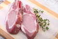 Raw pork chops, spices and rosemary on cutting board. Ready for cooking. Royalty Free Stock Photo