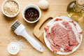 Raw pork loin chops, bread crumbs, salt, pepper, oil, egg on woo Royalty Free Stock Photo