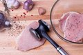 Raw pork schnitzel with meat tenderizer on wooden Royalty Free Stock Photo