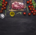 Raw pork steak for the grill, on a cutting board with vegetables and herbs, rosemary border ,place for text  on wooden rustic back Royalty Free Stock Photo