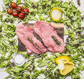 Raw pork steak on vintage cutting board with lettuce, cherry tomatoes, bell pepper, oil spices wooden rustic background top