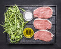 Raw pork steaks with green salad of arugula, butter and salt, protein and vitamins wooden rustic background top view close up Royalty Free Stock Photo