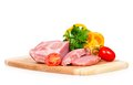 Raw pork with vegetables on a cutting board over white background Stock Photography