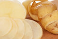 Raw potato peeled new with cleanings on a chopping board close up Stock Photos