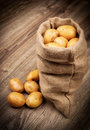 Raw potatoes in the sack on wooden background Royalty Free Stock Photography
