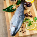 Raw rainbow trout on the board chopping with lemon and spices Royalty Free Stock Image