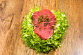Raw red beef with salad and pepper grains Royalty Free Stock Images