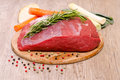 Raw roast of beef with condiments and root vegetables Royalty Free Stock Images