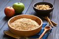 Raw rolled oats in wooden bowl with apples cinnamon sticks and a bowl of fruit crumble in the back photographed on dark wood with Royalty Free Stock Images