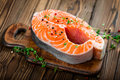 Raw salmon fish steak on wooden rustic background Royalty Free Stock Photo