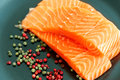 Raw salmon ready to cook close up on black surface and pepper corns plate Stock Images