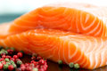 Raw salmon ready to cook close up on black surface and pepper corns plate Royalty Free Stock Photo