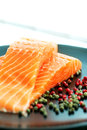 Raw salmon ready to cook copy space and pepper corns on plate close up with Stock Photography