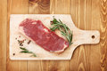Raw sirloin steak with rosemary and spices on cutting board Royalty Free Stock Photo