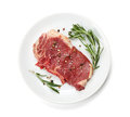 Raw sirloin steak with rosemary and spices on plate Royalty Free Stock Photo