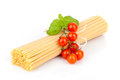 Raw spaghetti bunch of with basil leaves and cherry tomatoes on white background Stock Images