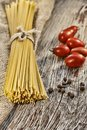 Raw spaghetti or fettuccine and cherry tomatoes on a wooden table. Rustic style .. Royalty Free Stock Photo