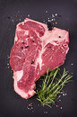 Raw t bone steak as closeup on a black slate Royalty Free Stock Images