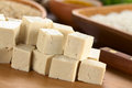 Raw tofu pieces cut in dices on wooden board with rice and other ingredients in the back selective focus focus on the front of the Stock Photo