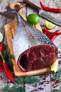 Raw tuna with spices fresh tail on wooden board red hot chili pepper fresh lime and dill selective focus Stock Image