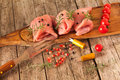 Raw turkey breast fillets wooden board with pieces of meat decorated with cherry tomatoes rosemary juniper berries and pomegranate Royalty Free Stock Image