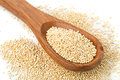 Raw, uncooked, whole quinoa seed in wooden spoon