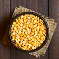 Raw yellow split peas in small bowl photographed overhead on dark wood with natural light selective focus focus on the top of the Royalty Free Stock Photo