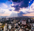 Rays of light shining through dark clouds above bangkok city thailand Stock Photo