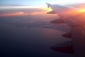 Rays of light in twilight sunset purple orange sky view from window airplane wings Royalty Free Stock Photo