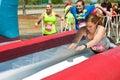 Raza de obstáculo loca de dive onto wet slide at de las mujeres Fotos de archivo libres de regalías